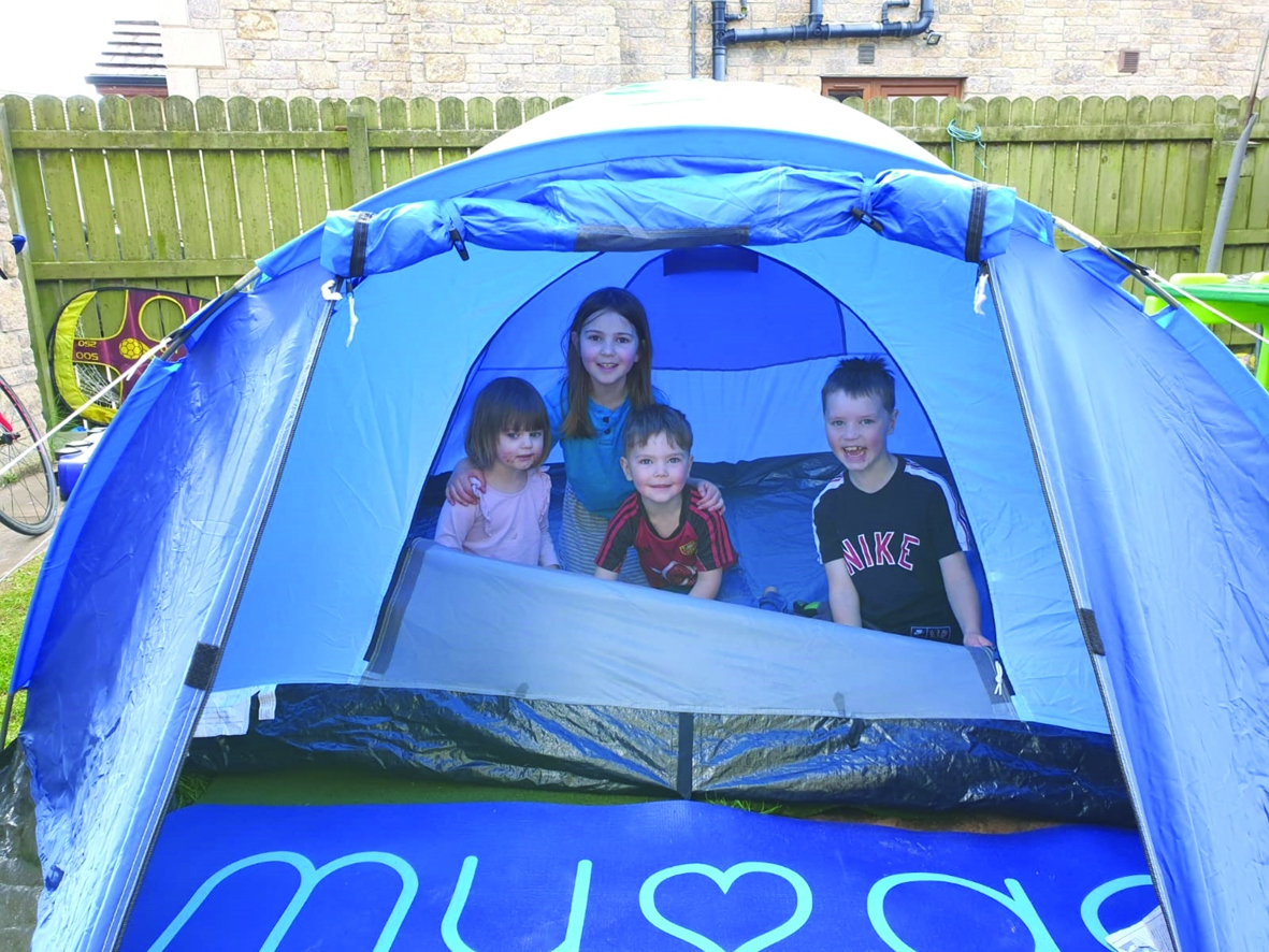 A family in a blue tent
