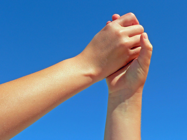 hands clasped together in front of a blue sky