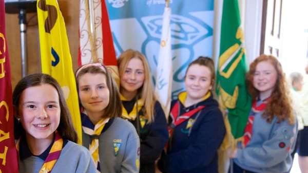 Girl Guides and Rangers holding Unit flags